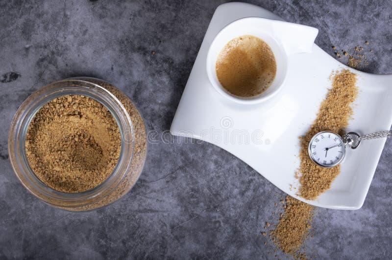 Weiße PorzellanKaffeetasse mit braunem Zucker, Zuckerschüssel und Taschenuhr, die anzeigt, dass es Zeit ist, einen heißen Kaffee  stockfotografie