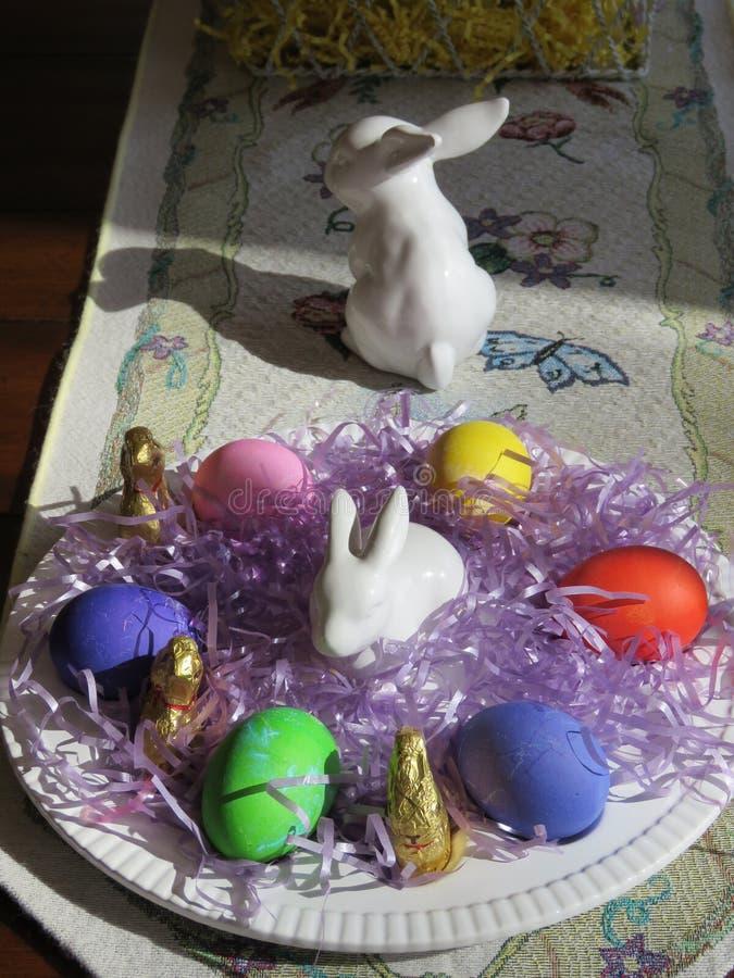 Weiße Porzellankaninchen, mehrfarbige hart gesotten Eier und kleine Schokoladenhäschen, oh mein! stockfoto