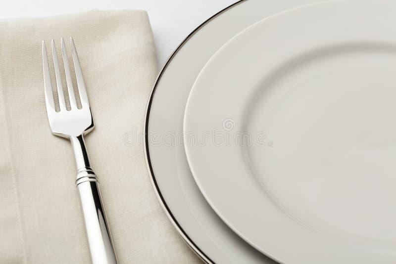 Weiße Porzellanplatten, Gabel und Leinenstoffserviettengedeck stockbild