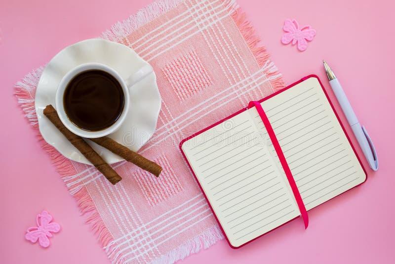 Weiße Porzellanschale mit Kaffee, zwei Kaffeerollen auf Untertasse mit gewelltem Rand und Papiernotizbuch mit Kugelschreiber auf  stockfoto