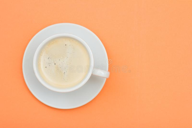 Weiße Porzellanschale schwarzer Kaffee auf Untertasse auf Pfirsichfarbbac lizenzfreies stockfoto