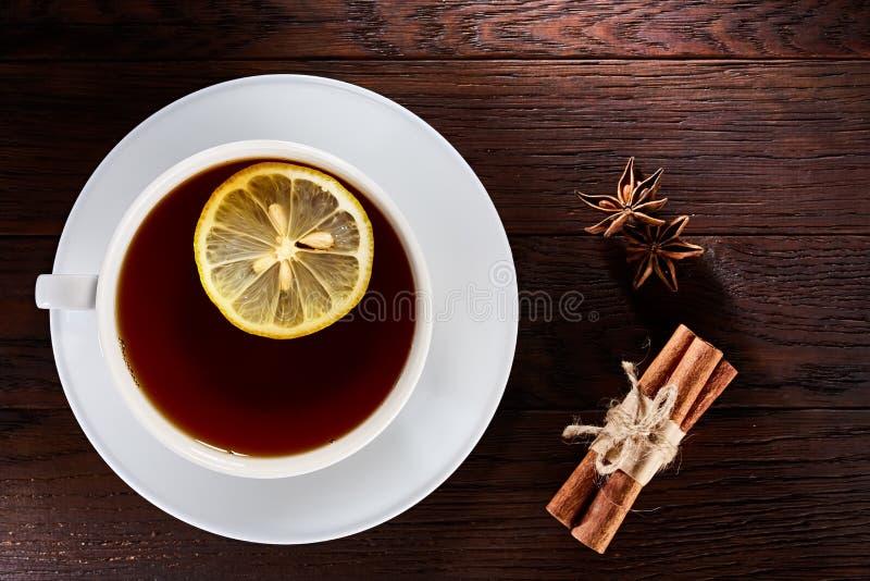 Weiße Porzellantasse tee mit Zimtstangen, Zitrone, tadellosen Blättern und Teesieb stockbild
