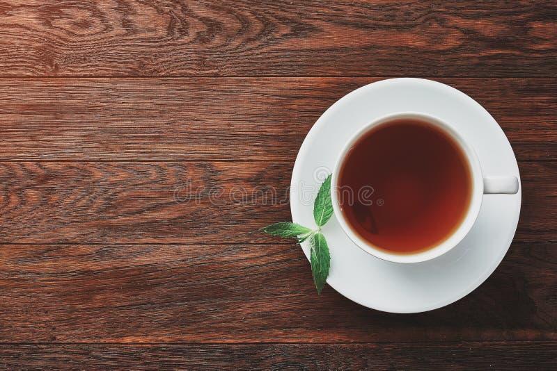 Weiße Porzellantasse tee mit Zimtstangen, Zitrone, tadellosen Blättern und Teesieb lizenzfreie stockbilder