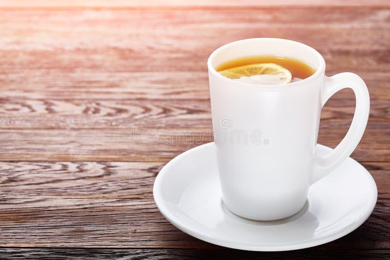 Weiße Porzellantasse tee mit Zimtstangen, Zitrone, tadellosen Blättern und Teesieb lizenzfreies stockfoto