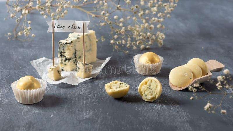 Weiße Pralinen mit Blauschimmelkäse auf grauem Hintergrund Köstliche Süßigkeiten für Feinschmecker lizenzfreies stockfoto