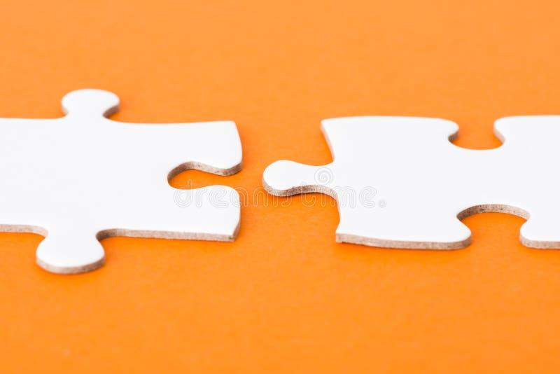 Weiße Puzzlespielteile auf orange Hintergrund lizenzfreies stockfoto
