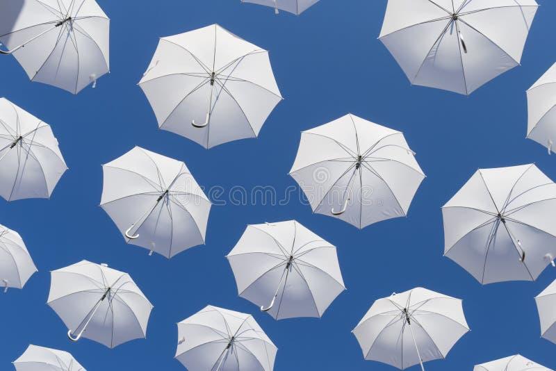 Weiße Regenschirme auf blauem Himmel lizenzfreies stockfoto