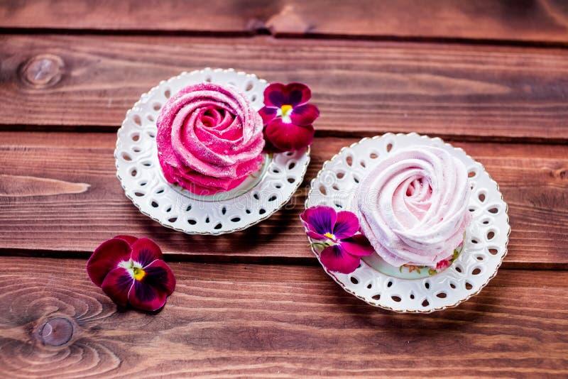 Weiße, rosa Zefireibische der Süßspeise auf Lehmplatte und rustikaler hölzerner Hintergrund Eibisch, Meringe, Zefir stockbilder
