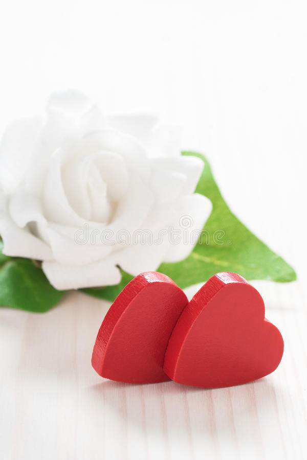 Weiße Rose mit zwei roten Herzen stockbild
