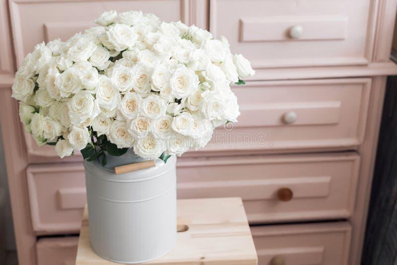 Weiße Rosen des Weinleseinnenausstattungsrosapastellwandschranks im Blecheimer lizenzfreie stockfotos