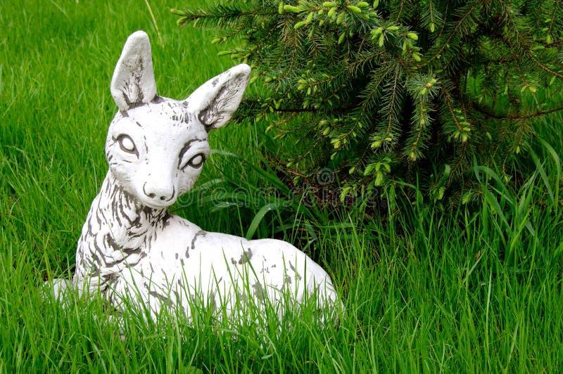 Weiße Rotwild bambi Steinskulptur, die auf dem grünen Rasen liegt lizenzfreie stockfotografie