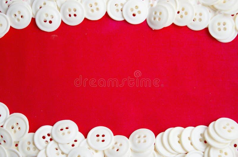 Weiße runde Knöpfe liegen auf der roten Oberfläche der Spitzen- und unteren Nahaufnahme stockbild