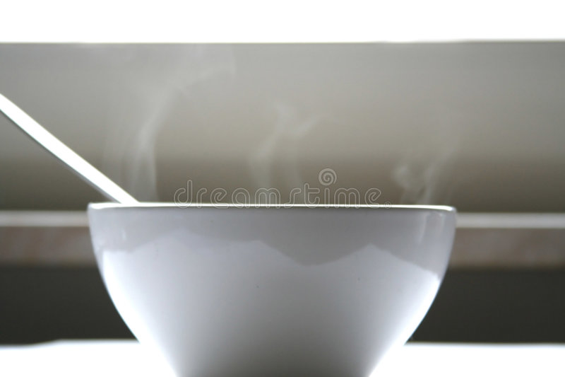 Weiße Schüssel mit dämpfender Suppe und Löffel lizenzfreies stockbild