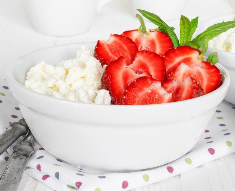 Wei?e Sch?ssel mit frischen roten reifen Erdbeeren und nat?rlichem H?ttenk?se stockfotografie