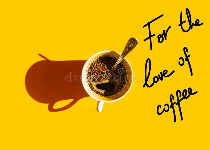 Weiße Schale frisch gebrauter Kaffee mit schäumendem crema Teelöffel auf Draufsicht des festen gelben Hintergrundes Handbeschrift lizenzfreies stockbild