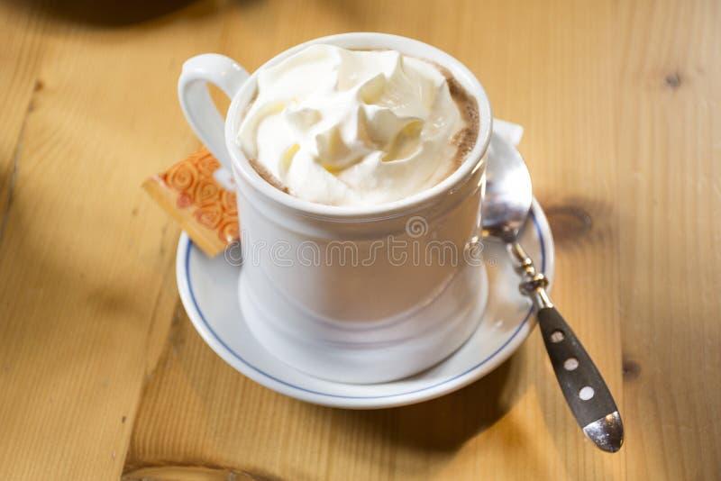 Weiße Schale mit Belagsschlagsahneaufschlag der heißen Schokolade mit Zuckertasche stockbild