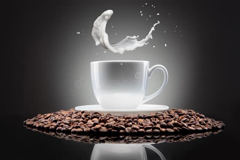 Weiße Schale mit Kaffeebohnen und Milch spritzt stockfoto