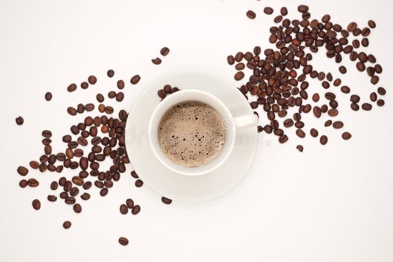 Weiße Schale mit schwarzem klassischem Kaffee und einer Untertasse unter Kaffeebohnen Draufsicht, lokalisiert auf weißem Hintergr stockfotos
