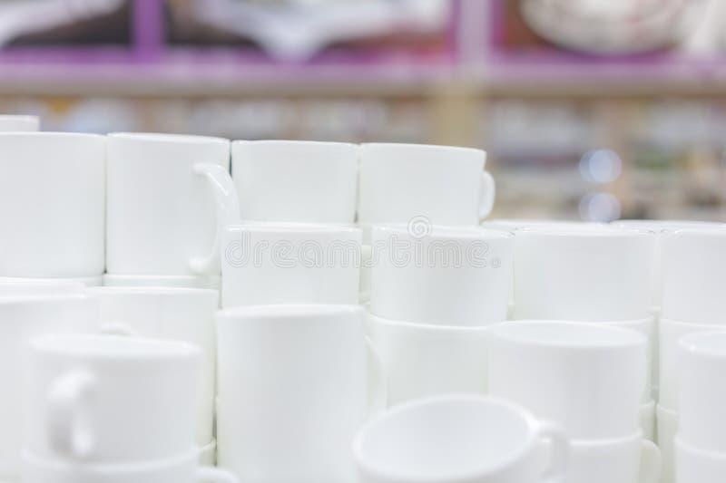 Weiße Schalen im Regal im Speicher Weiße keramische Kaffeetassen und untertassen auf Regalen Regale mit Küchengeräten stockfoto