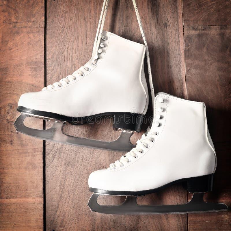 Weiße Schlittschuhe für Eiskunstlauf, hängend am hölzernen Hintergrund stockbilder