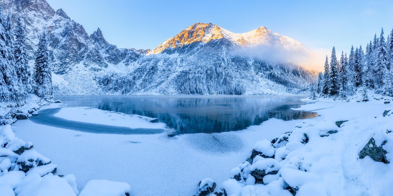 Weiße Schneeflocken auf einem blauen Hintergrund Sonniger Weihnachtsmorgen in den Bergen Morskie-oko See, Tatras, Polen stockfoto