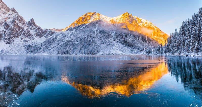 Weiße Schneeflocken auf einem blauen Hintergrund Winterlandschaft mit den Bergen reflektiert im klaren gefrorenen See lizenzfreies stockfoto