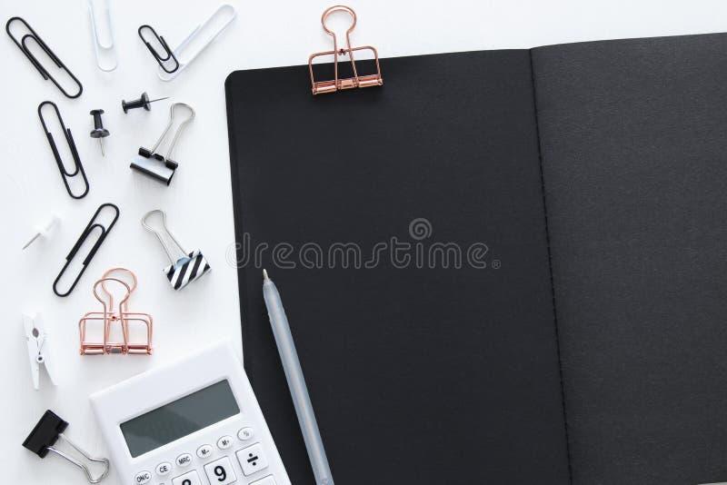 Weiße Schreibtischtabelle mit Taschenrechner, offenem Notizbuch mit schwarzen Seiten und anderem Büroartikel Beschneidungspfad ei lizenzfreie stockbilder