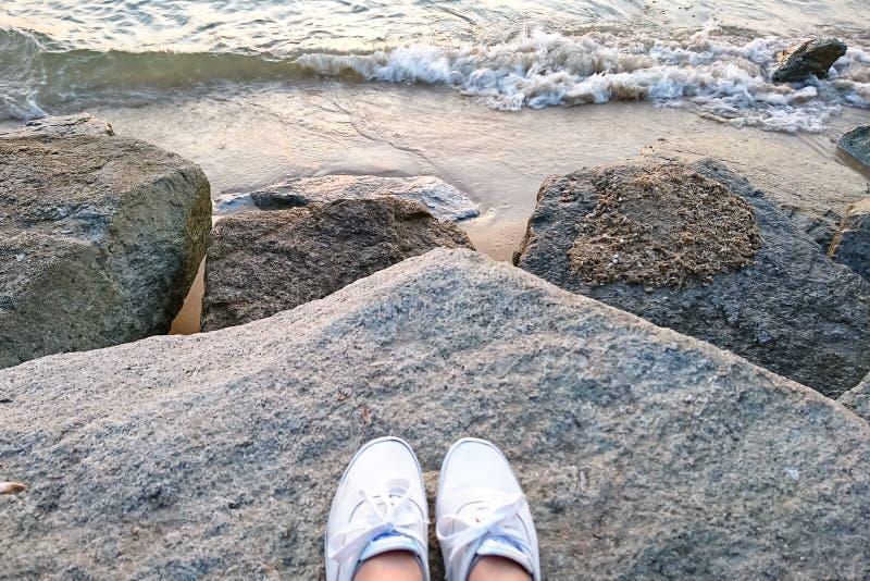 Weiße Schuhe sind auf den Felsen oder der Masse Hinten ist es die Ansicht des Strandes, des Sandes und des Meeres, das kleine Wel lizenzfreie stockfotografie