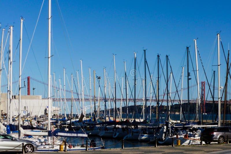 Weiße Segelboote in einer Bucht in Lissabon mit der Brücke am 25. April lizenzfreie stockfotos