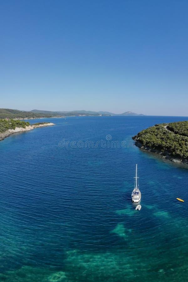Weiße Segelschiffyacht in Meer im seichten Wasser nahe Ufer Luftbrummenansicht zum Segelboot lizenzfreie stockfotos
