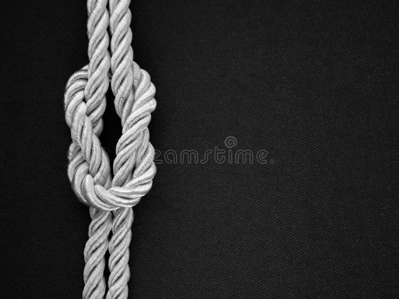 Weiße Seilgleichheit ein Knoten auf dem Schwarzen stockfoto