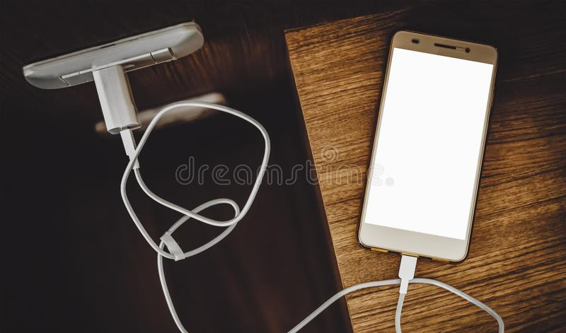 Weiße Smartphoneaufladung des leeren Bildschirms lizenzfreie stockbilder