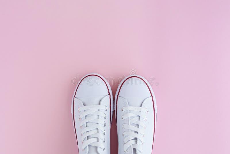 Weiße sneackers auf rosa Hintergrund lizenzfreie stockfotografie