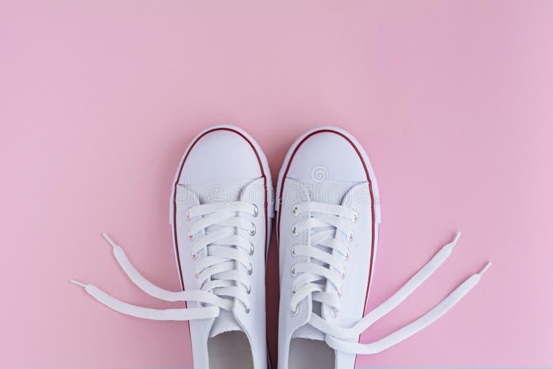 Weiße sneackers auf rosa Hintergrund lizenzfreie stockbilder