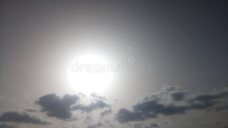 Weiße Sonne hinter grauen clauds selten in der Ansicht stockfotografie