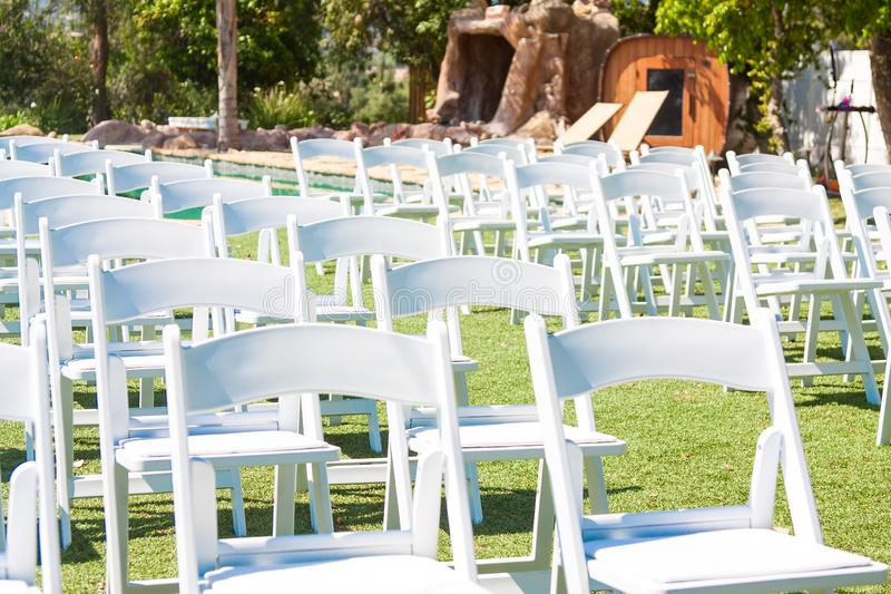 Weiße Stühle auf grünem Gras Vorbereiten für die Heiratszeremonie im Freien lizenzfreies stockfoto