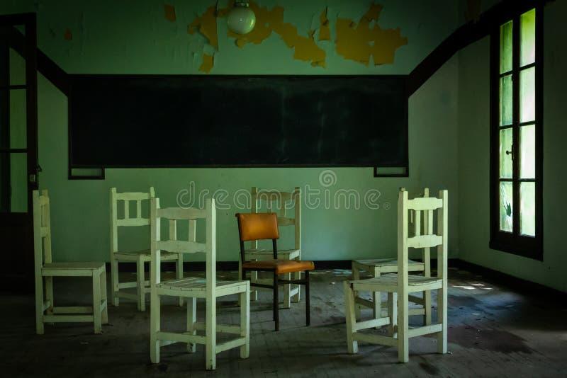 Weiße Stühle in den Kreisen, die einen orange Stuhl umgeben Schwarzes Brett auf der Wand lizenzfreie stockbilder