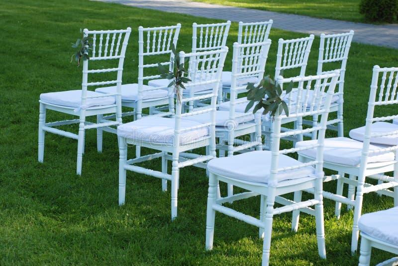 Weiße Stühle an der Hochzeits-Zeremonie-grünes Gras-Hintergrund-Partei im Freien feiern Hochzeits-Ereignis stockfoto