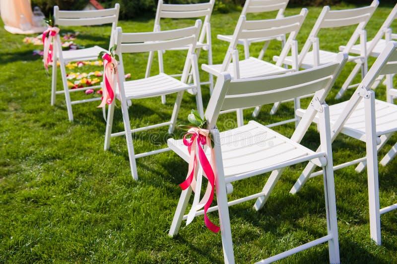 Weiße Stühle für Gäste der Hochzeitszeremonie stockfoto