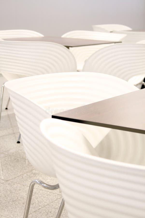 Weiße Stühle mit Tabellen lizenzfreies stockfoto