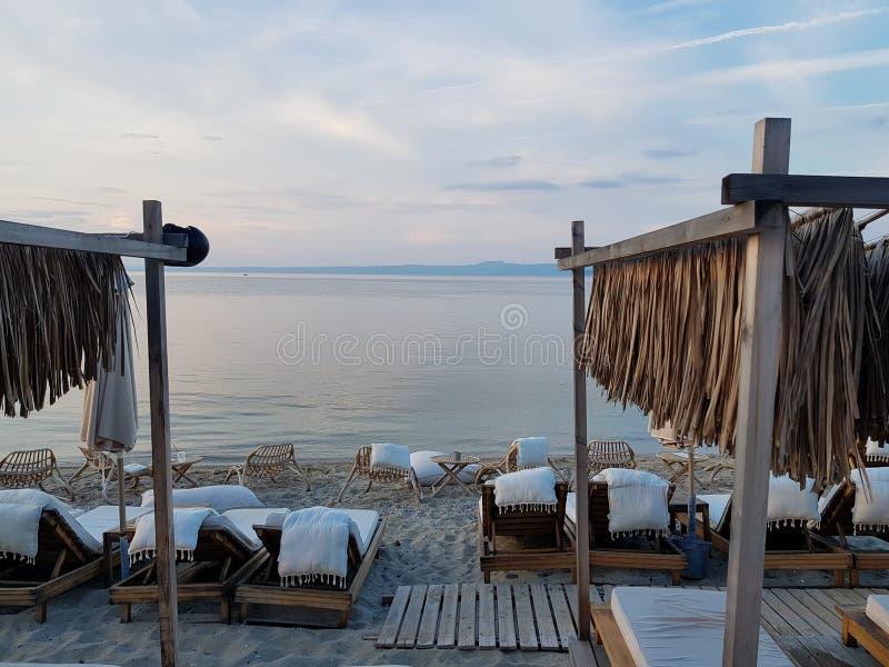 Weiße Stühle und Betten auf Küste nahe schönem blauem Meer stockfoto