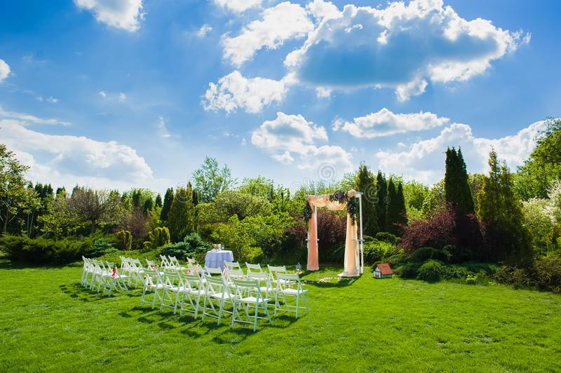 Weiße Stühle vor schönem Hochzeitsbogen stockfoto