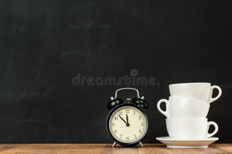 Weiße Staplungskaffeetassen mit Retro- Wecker stockfoto