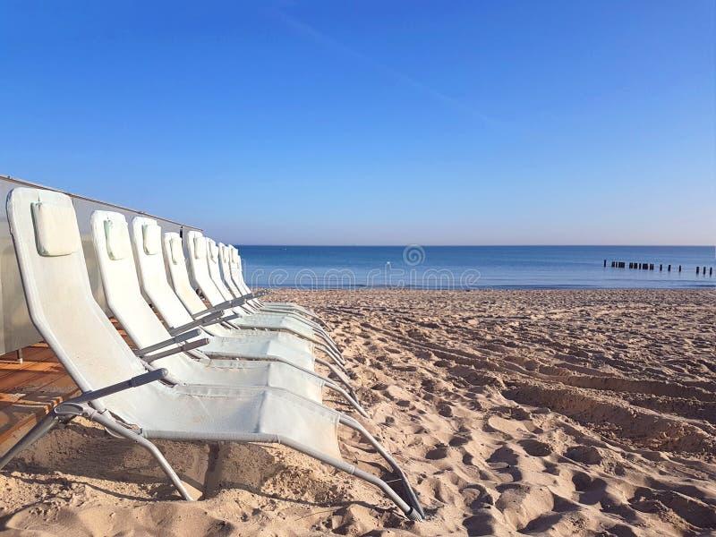 Weiße Strandstühle auf Strand in Ostsee stockbilder