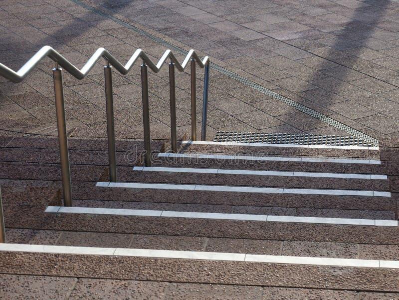 Weiße Streifen auf Abstiegschritten mit rostfreier Handschiene lizenzfreie stockfotografie