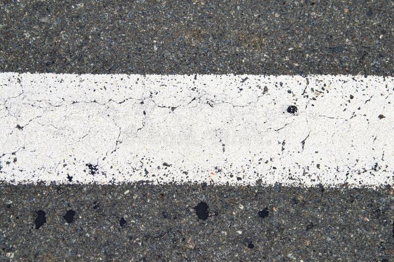 Weiße Streifenfahrbahnmarkierungen auf der Asphaltstraße lizenzfreie stockfotografie