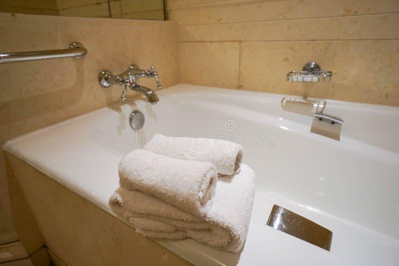 Weiße Tücher auf Badewanne im Badezimmer lizenzfreie stockfotografie