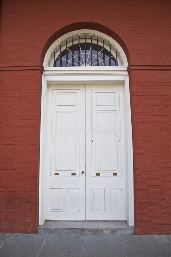 Weiße Tür, rotes Gebäude lizenzfreies stockbild