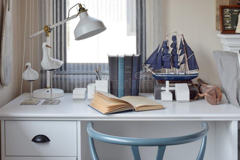 Weiße Tabelle mit Holzstuhlbüchern und -lampe im modernen Arbeitsbereich stockfoto