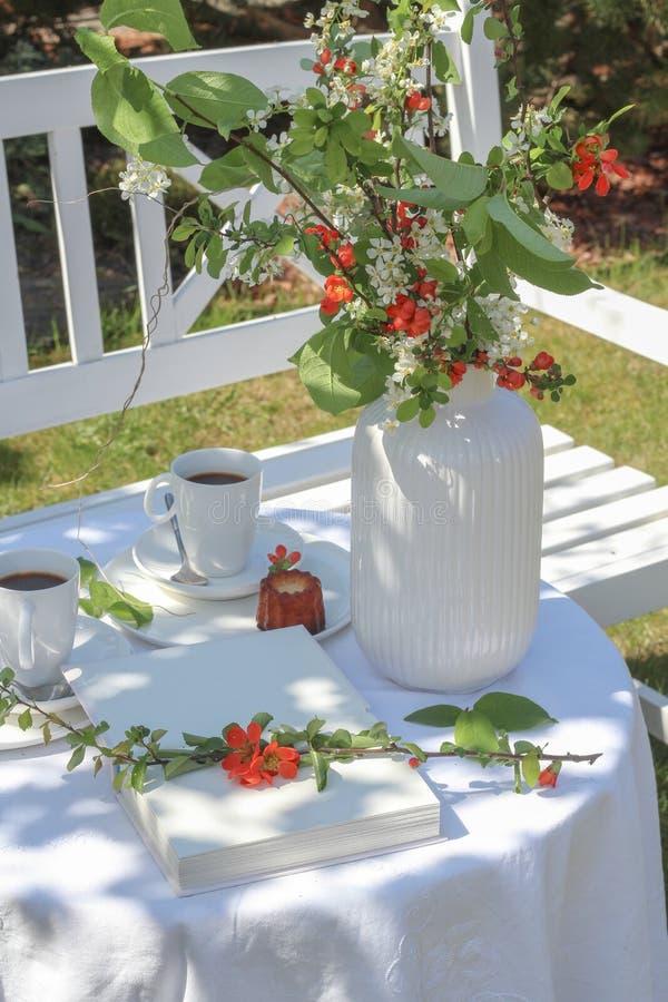 Weiße Tabelle mit Kaffee, caneles und Blumen diente im Garten stockfoto